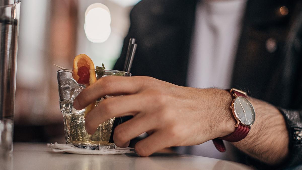 Imagen ilustrativa de un hombre con un coctel en un bar